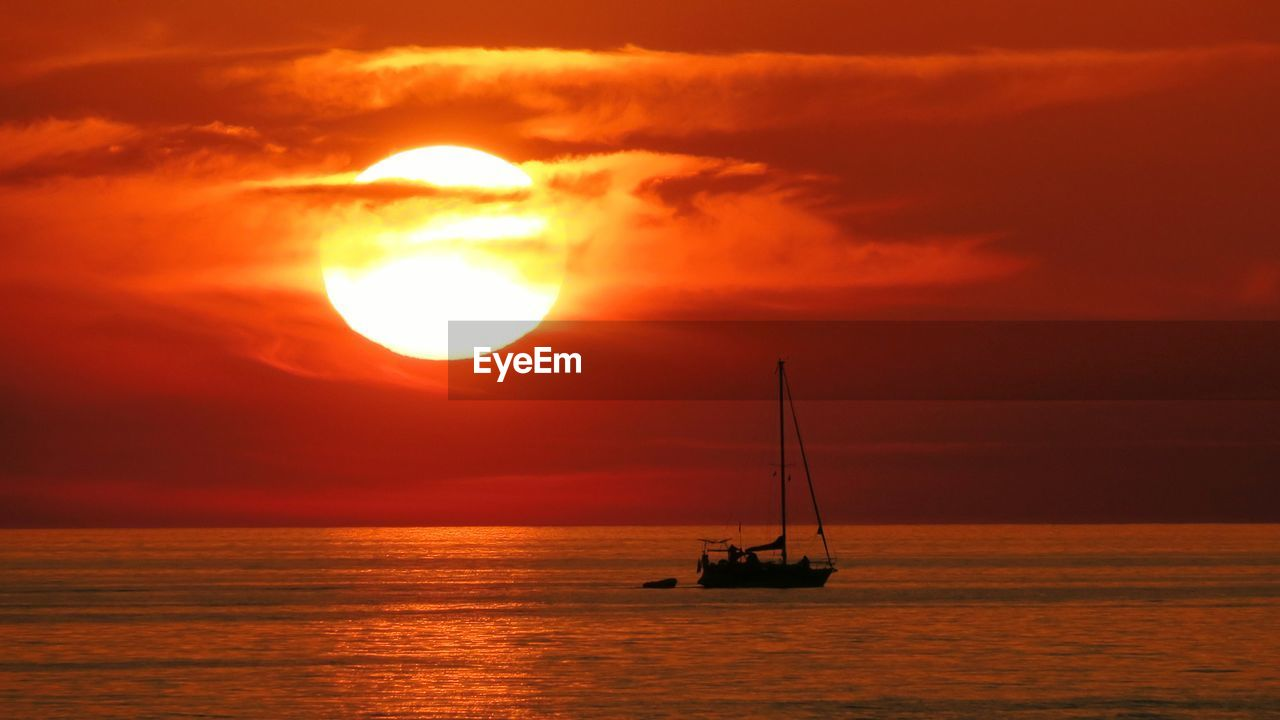 sunset, sun, orange color, beauty in nature, sea, sky, scenics, nature, water, cloud - sky, waterfront, idyllic, tranquil scene, nautical vessel, tranquility, horizon over water, reflection, dramatic sky, sunlight, silhouette, no people, outdoors, mast, scenery