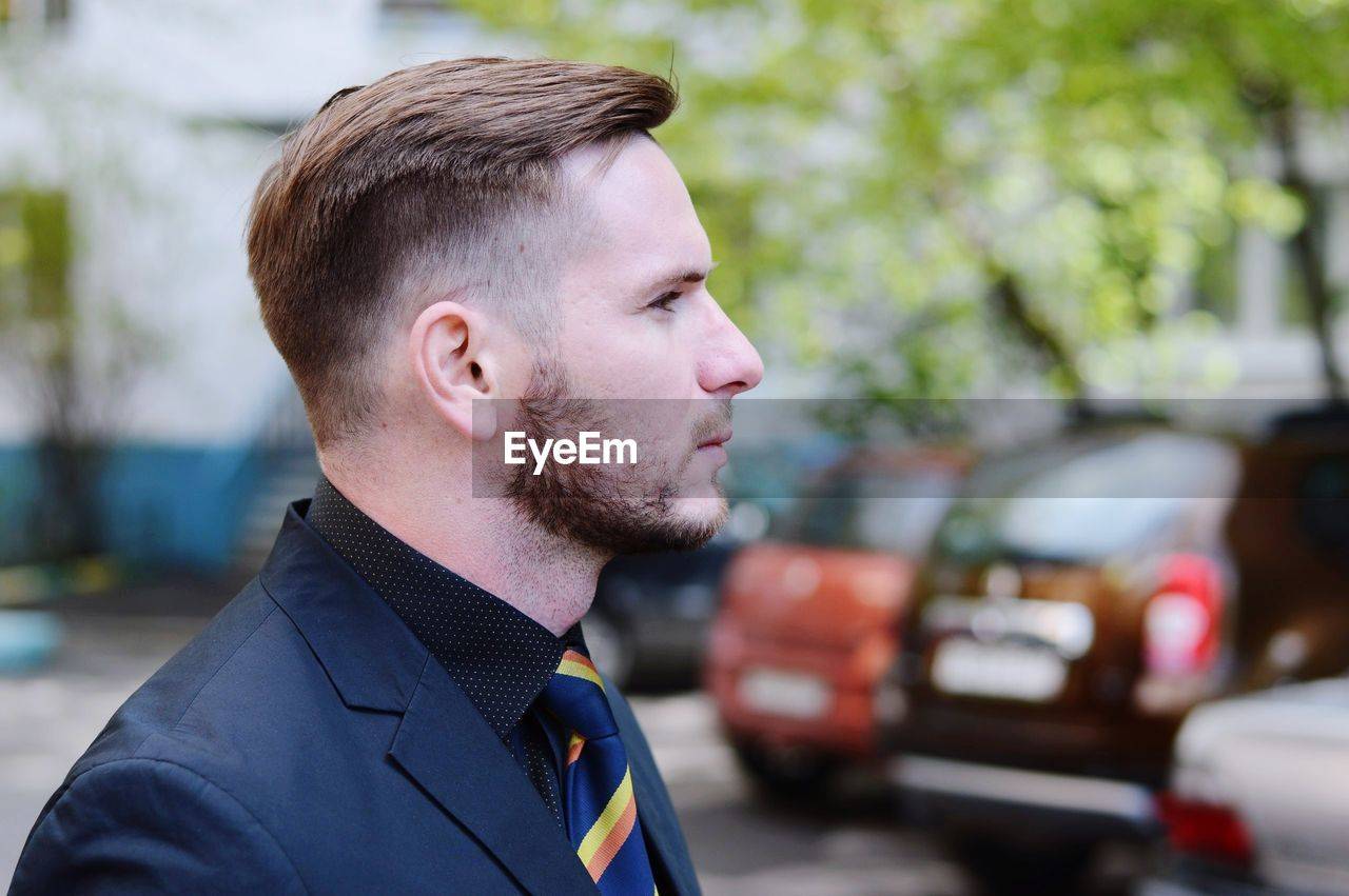 Side view of confident businessman in parking lot