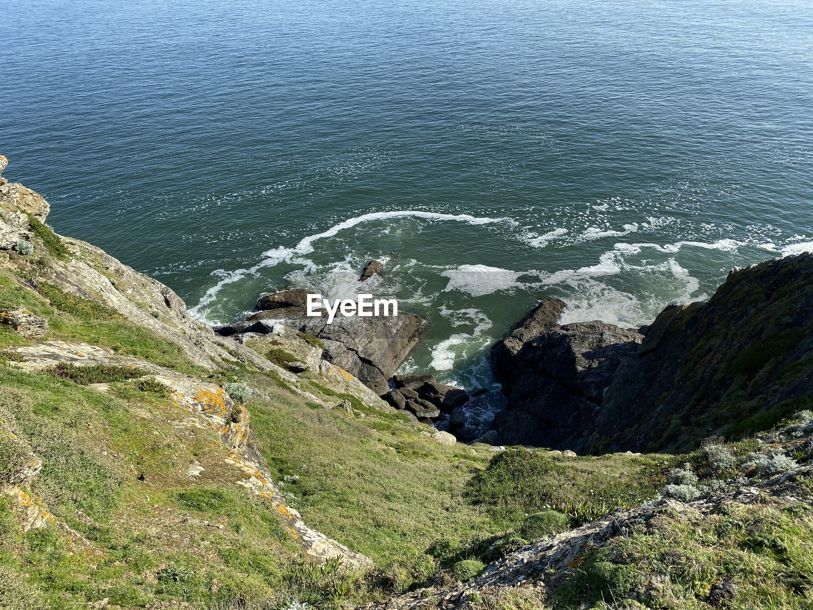 High angle view of rocks on sea shore