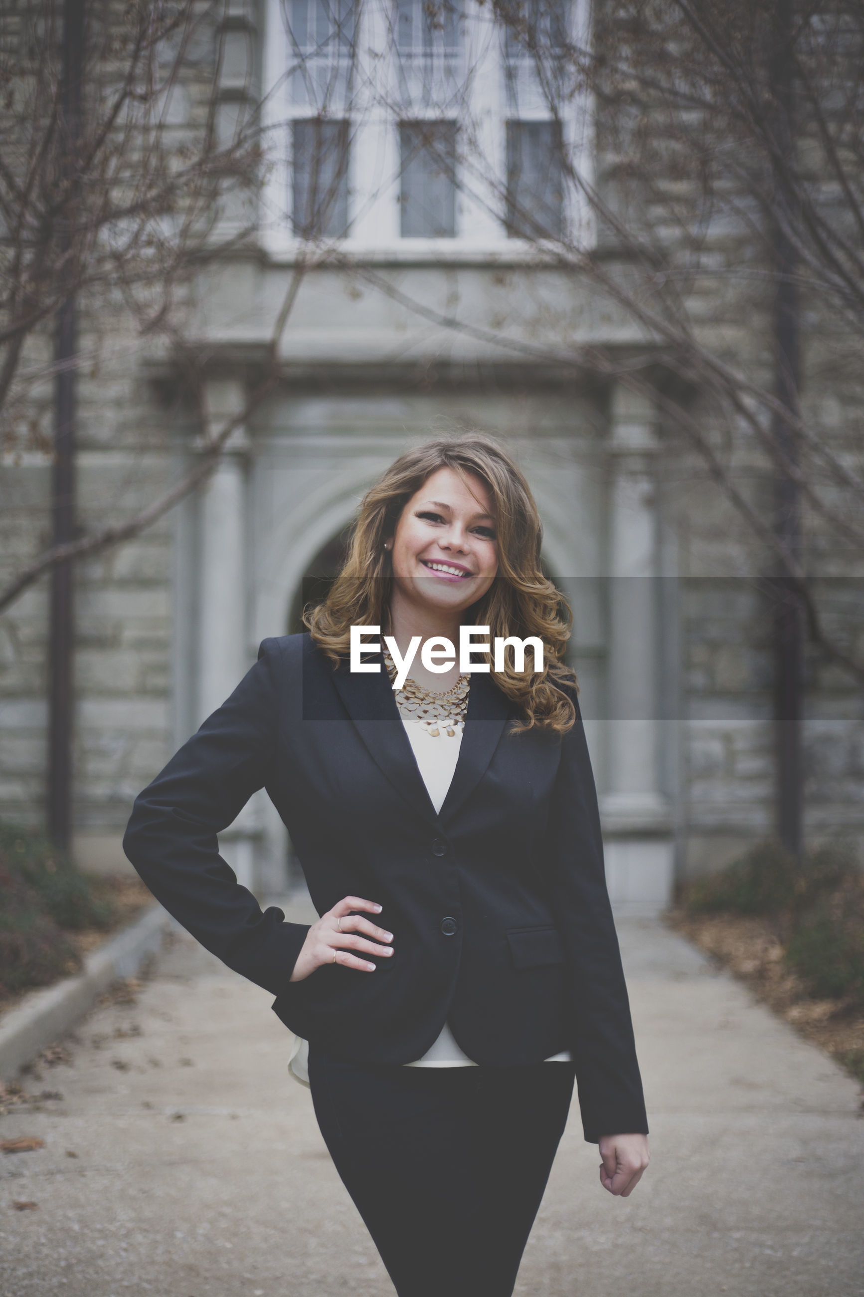Portrait of beautiful businesswoman against building