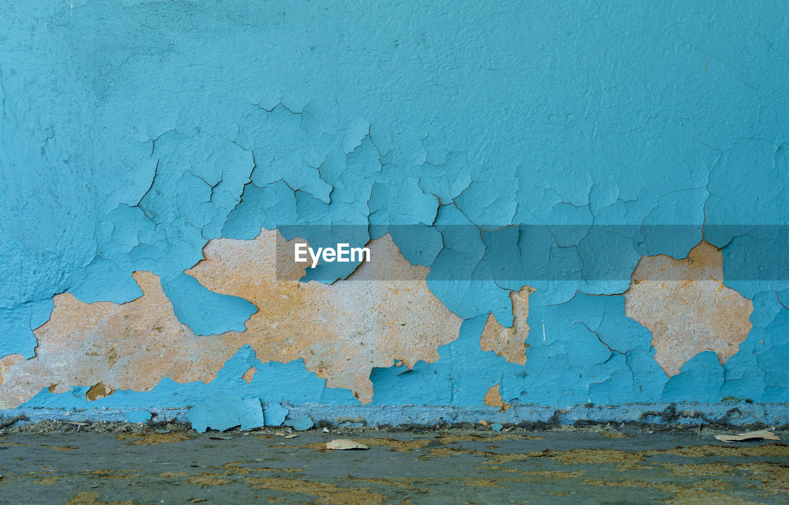 FULL FRAME SHOT OF WEATHERED WALL WITH BLUE PAINT