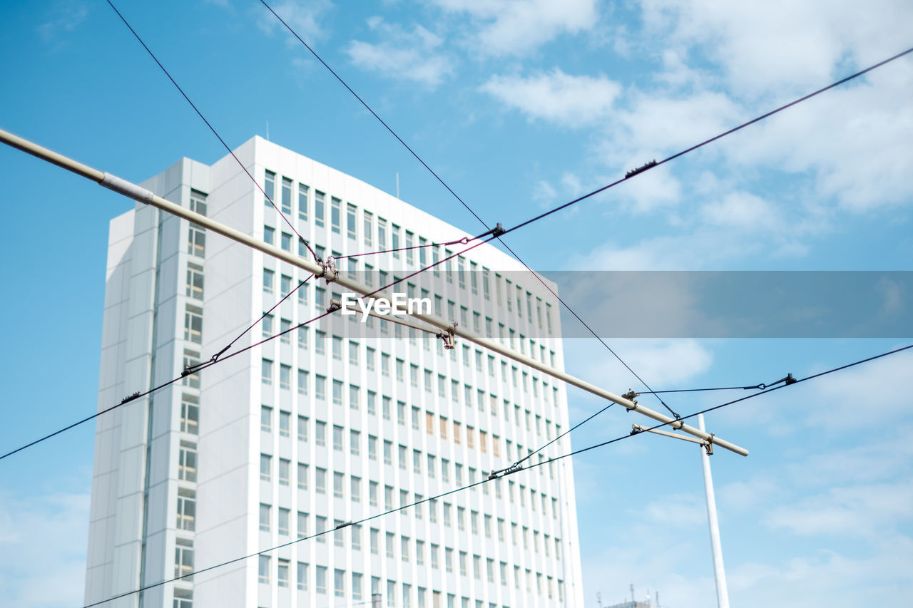 LOW ANGLE VIEW OF CABLES AGAINST BUILDINGS IN CITY
