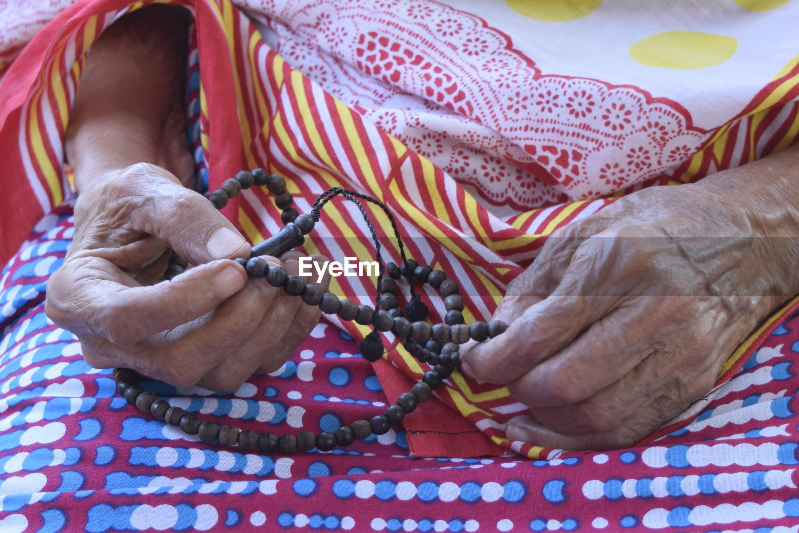 Close-up of senior woman holding prayer beads