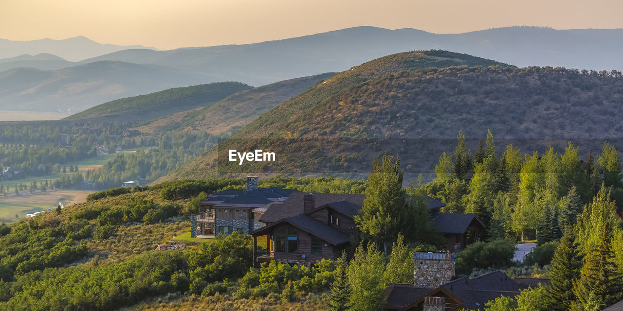 SCENIC VIEW OF TREES AND HOUSES BY MOUNTAINS