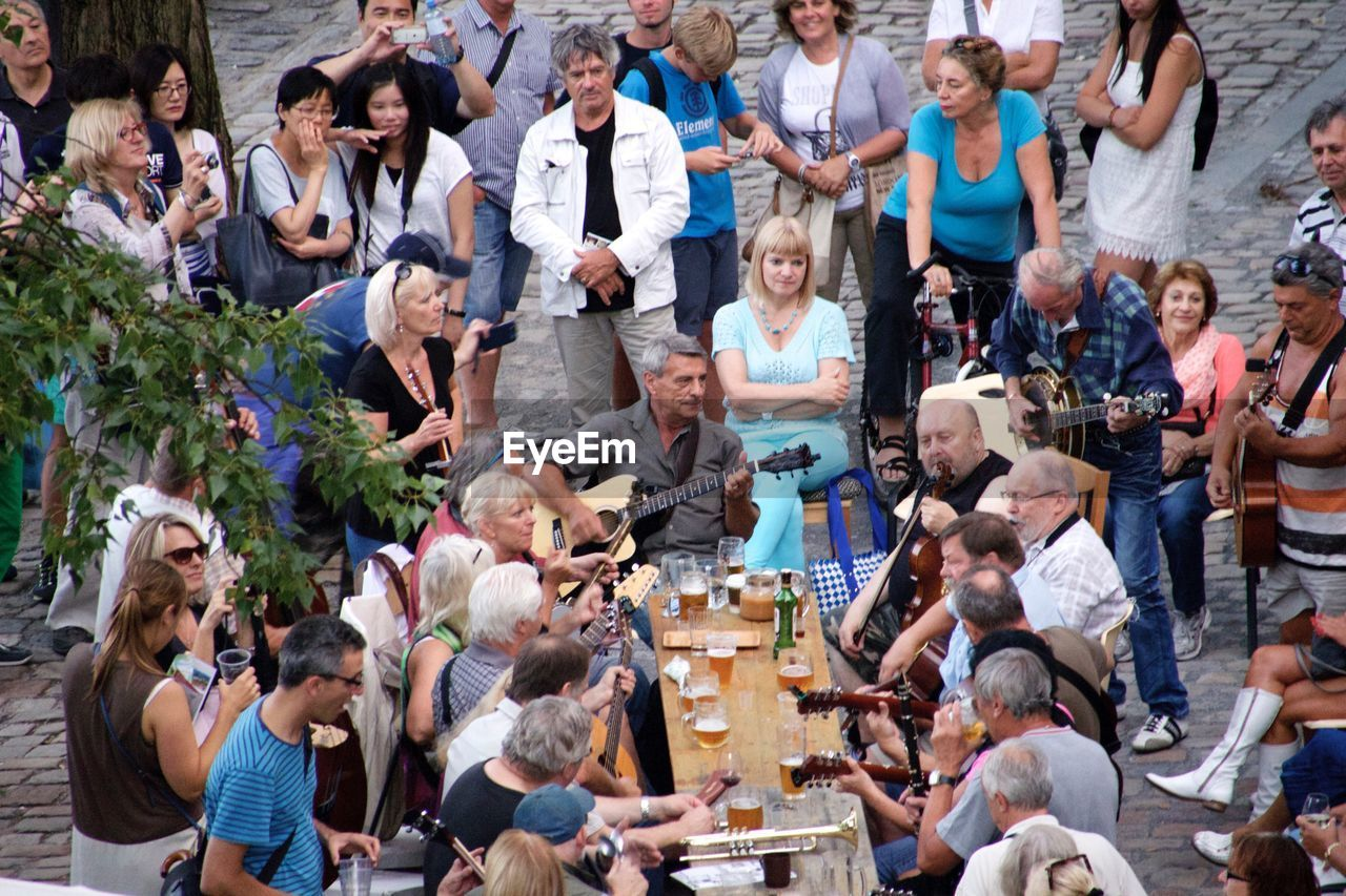large group of people, mature adult, mature women, sitting, crowd, high angle view, mature men, mid adult, women, men, young men, young adult, people, standing, young women, adult, togetherness, outdoors, day, adults only, real people, portrait, audience, musician