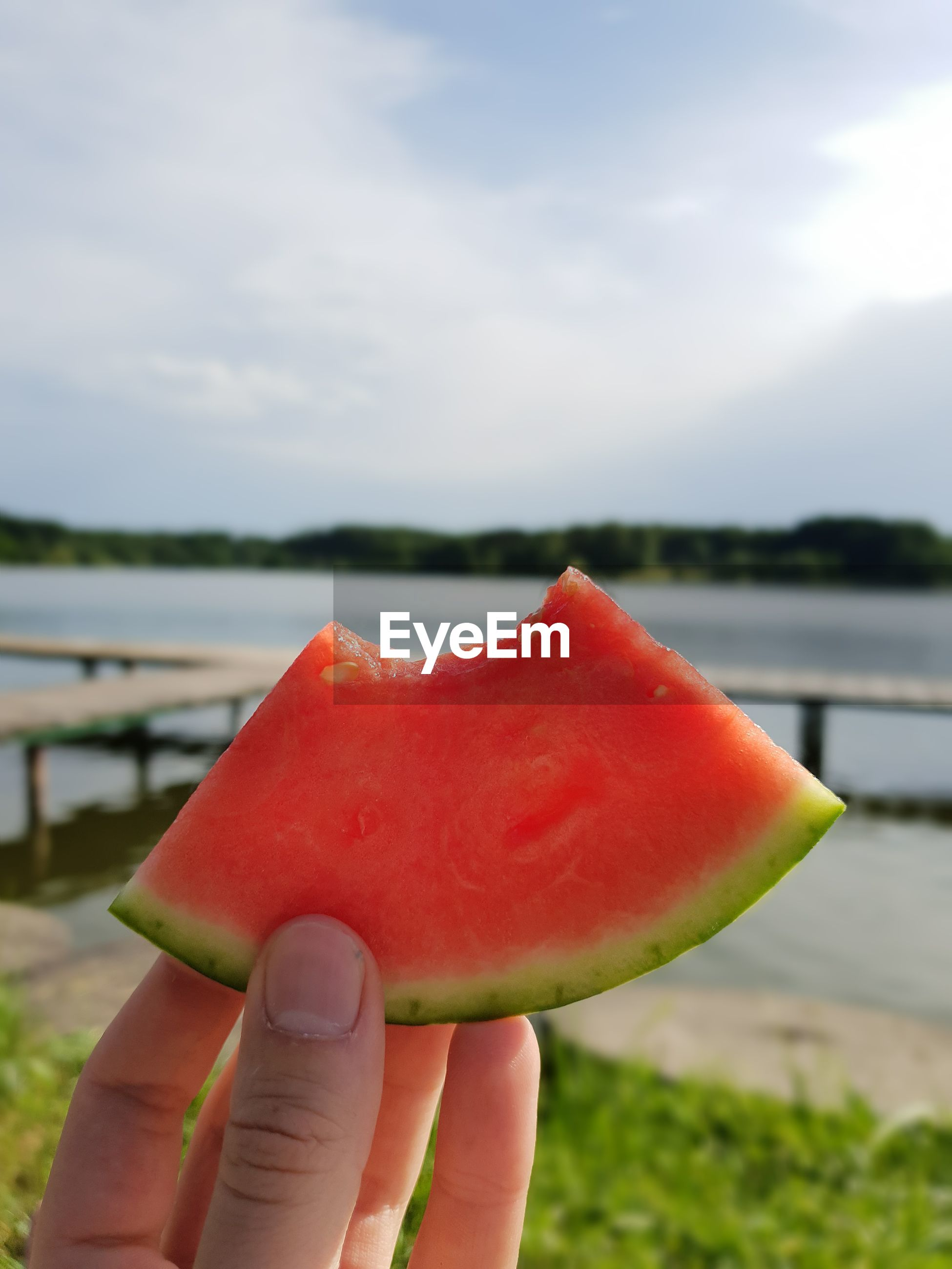 Cropped image of hand holding watermelon against sky