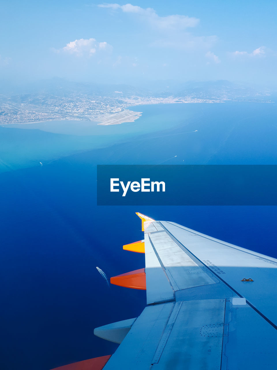 AERIAL VIEW OF SEA AND AIRPLANE FLYING IN SKY