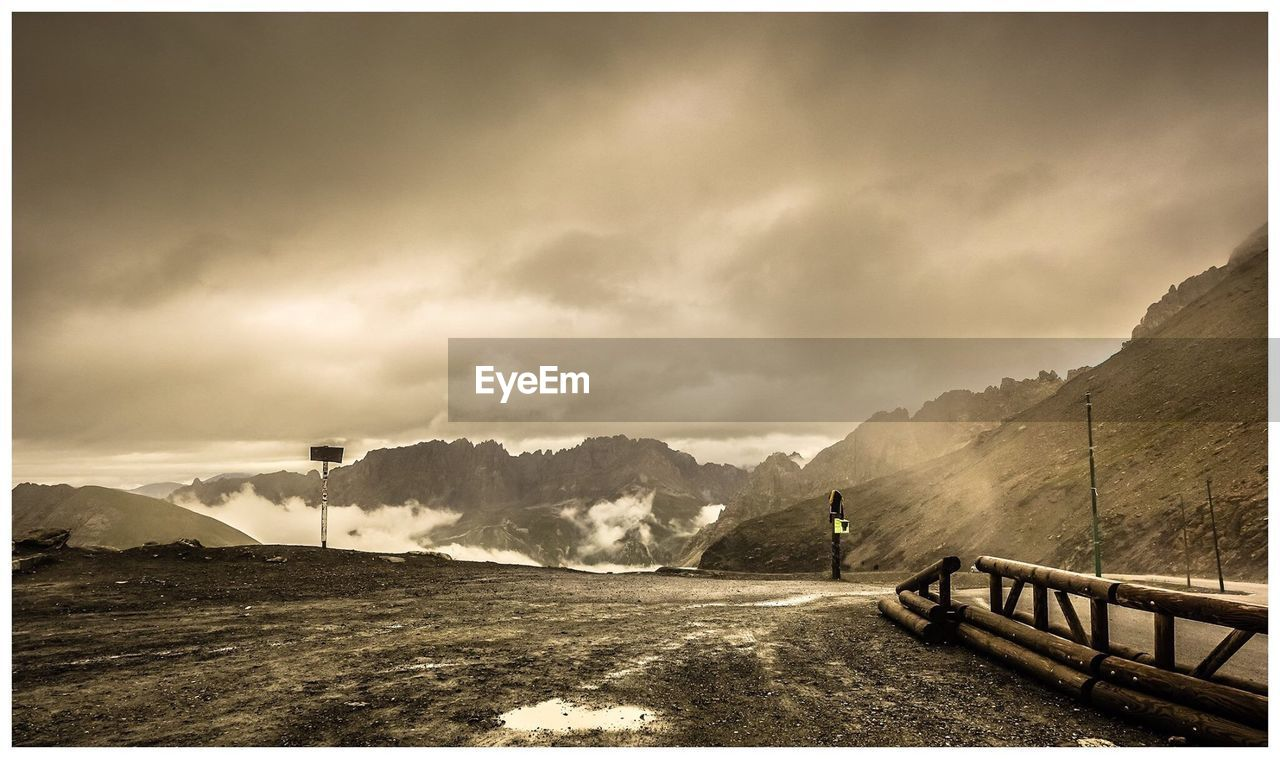 sky, mountain, cloud - sky, auto post production filter, beauty in nature, scenics - nature, nature, tranquility, tranquil scene, railing, transfer print, environment, landscape, mountain range, non-urban scene, day, outdoors, one person, leisure activity