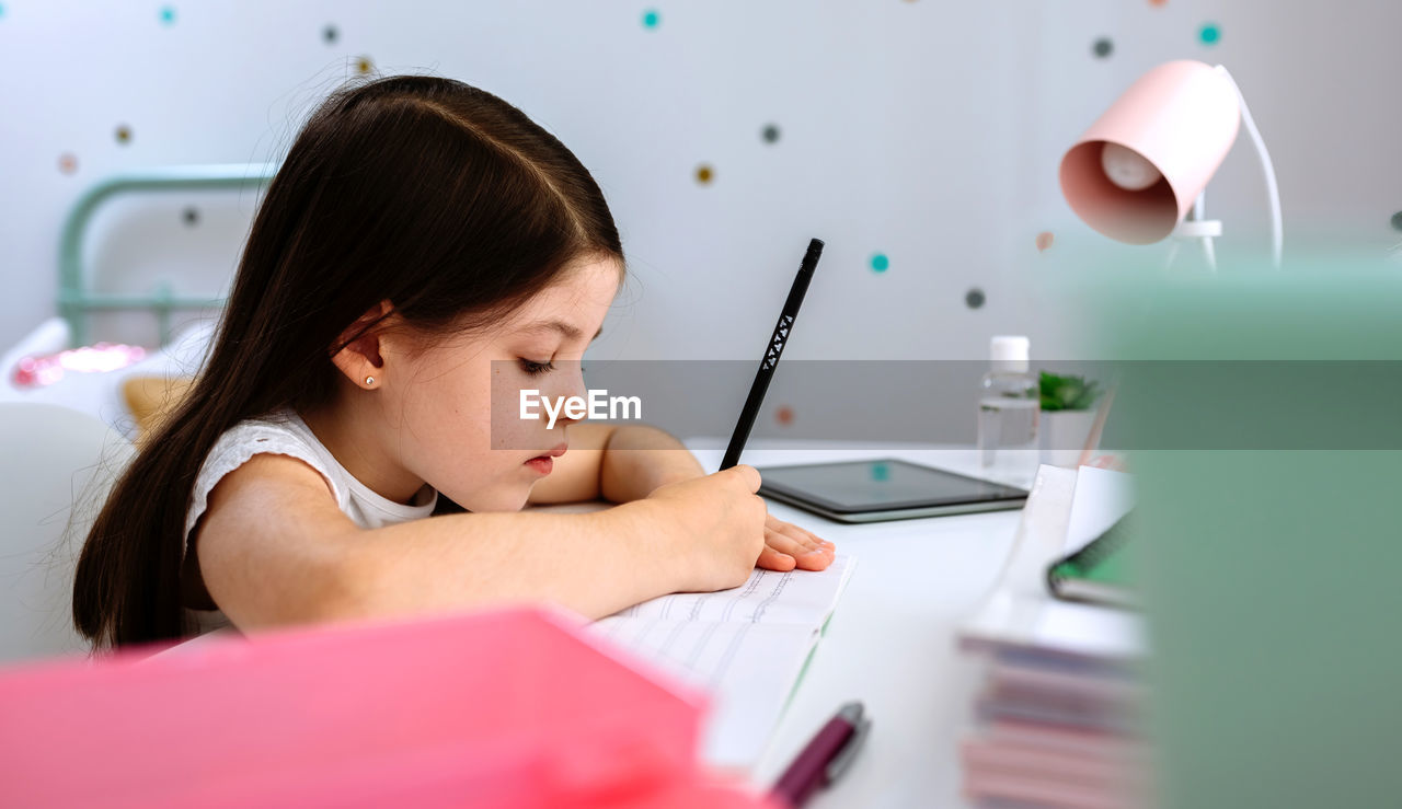 GIRL SITTING ON TABLE AT HOME
