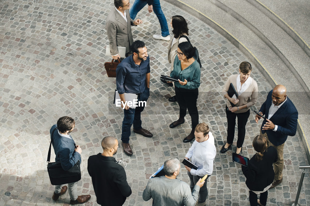 HIGH ANGLE VIEW OF PEOPLE WALKING IN FRONT OF FRIENDS