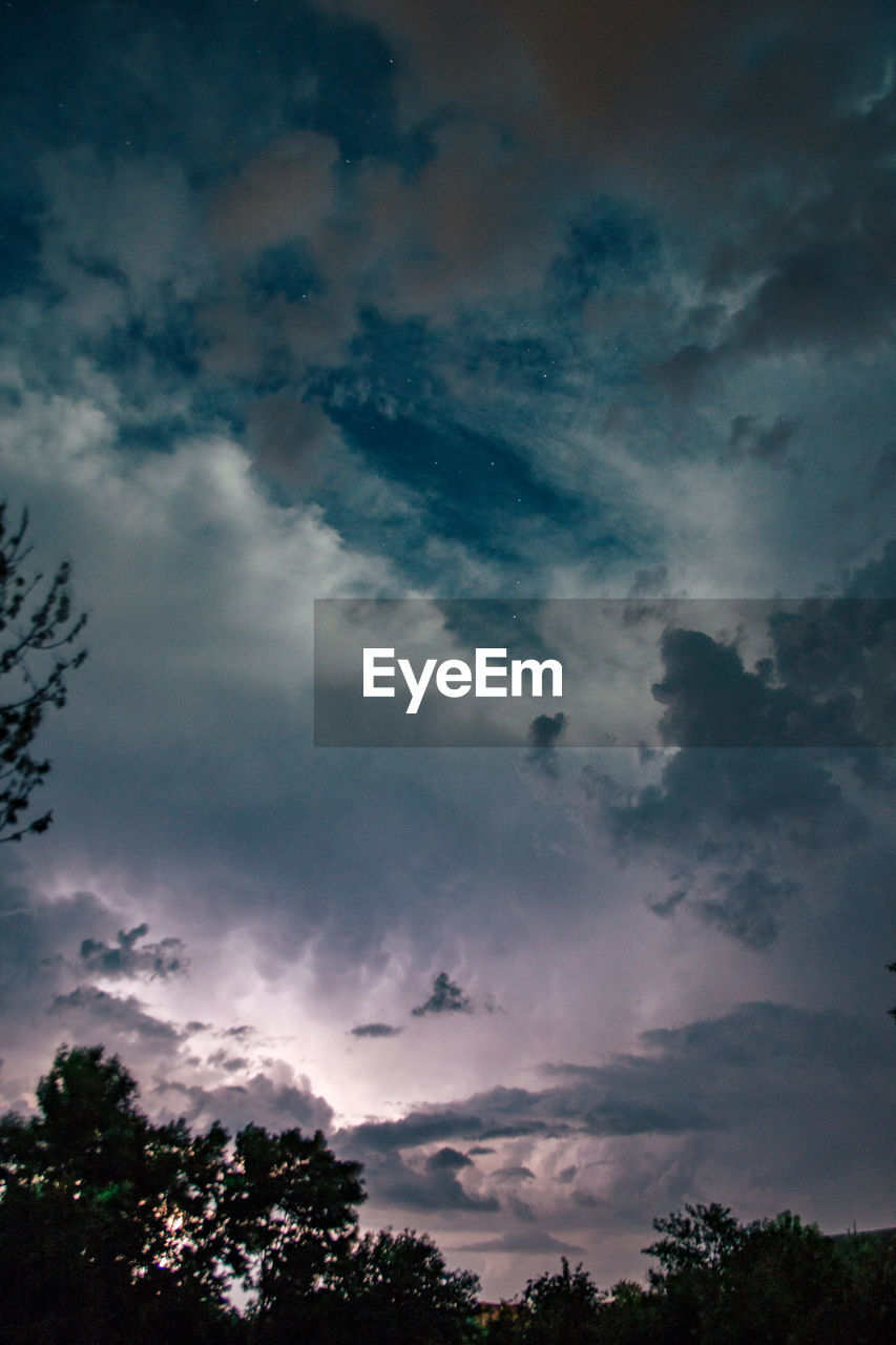 cloud - sky, sky, beauty in nature, tree, tranquility, low angle view, scenics - nature, tranquil scene, plant, nature, no people, silhouette, sunset, outdoors, cloudscape, idyllic, storm, dusk, overcast, ominous, meteorology
