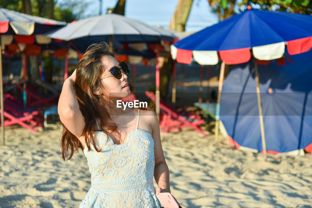 Woman In Sunglasses Standing Against Parasols At Beach