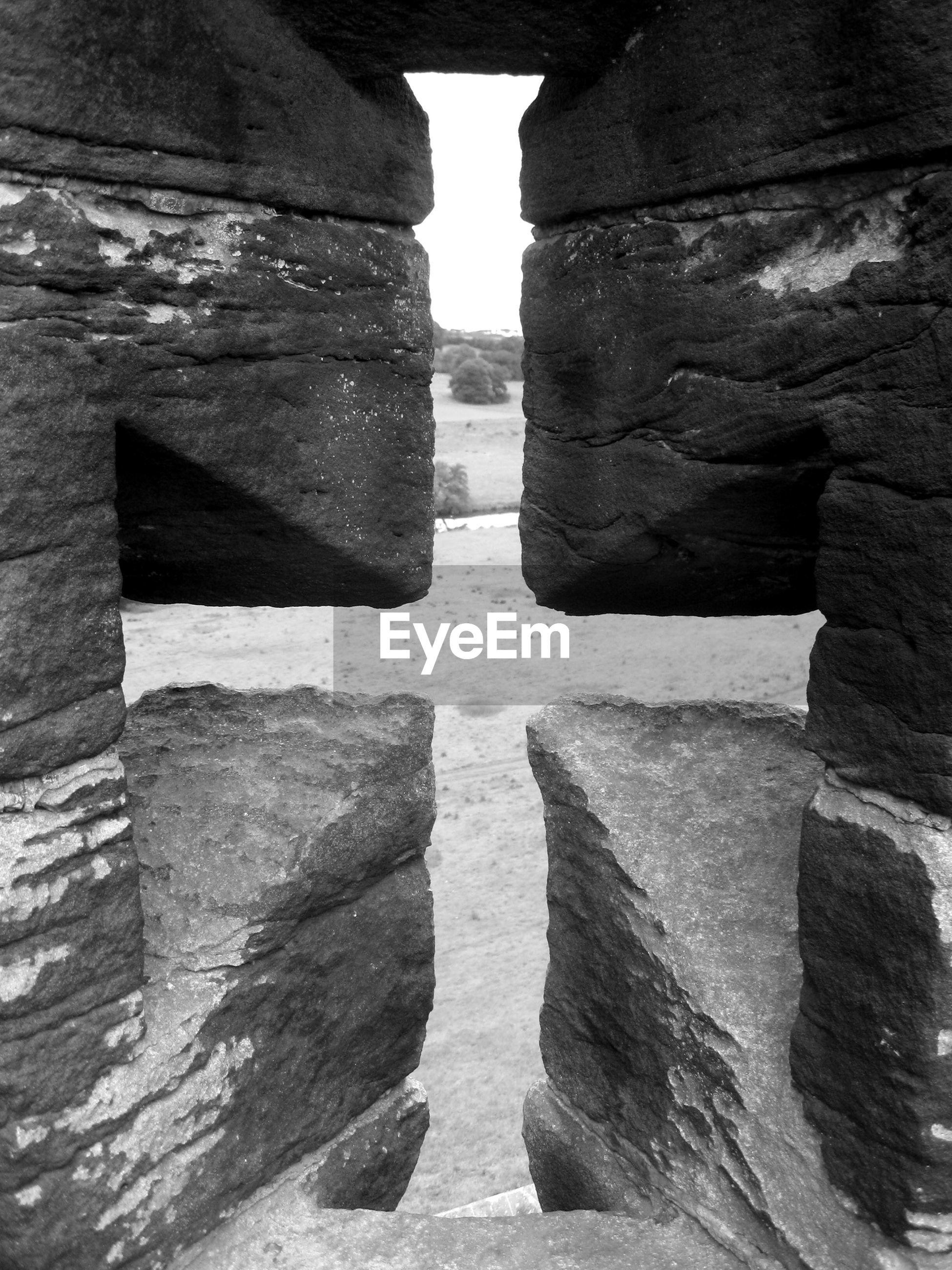 Landscape seen through cross shape passage in rocks of alnwick castle