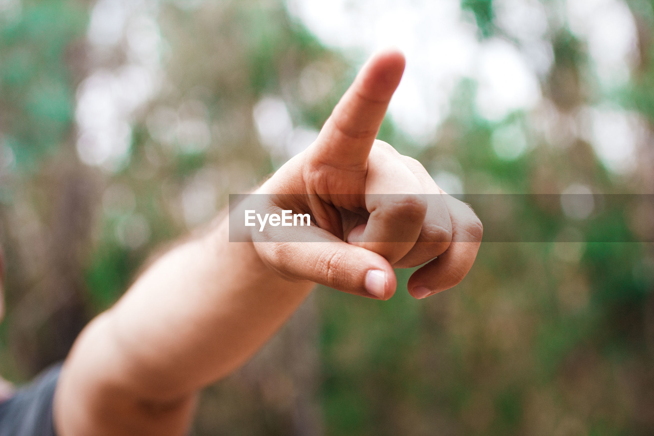 Close-up of man hand pointing in park