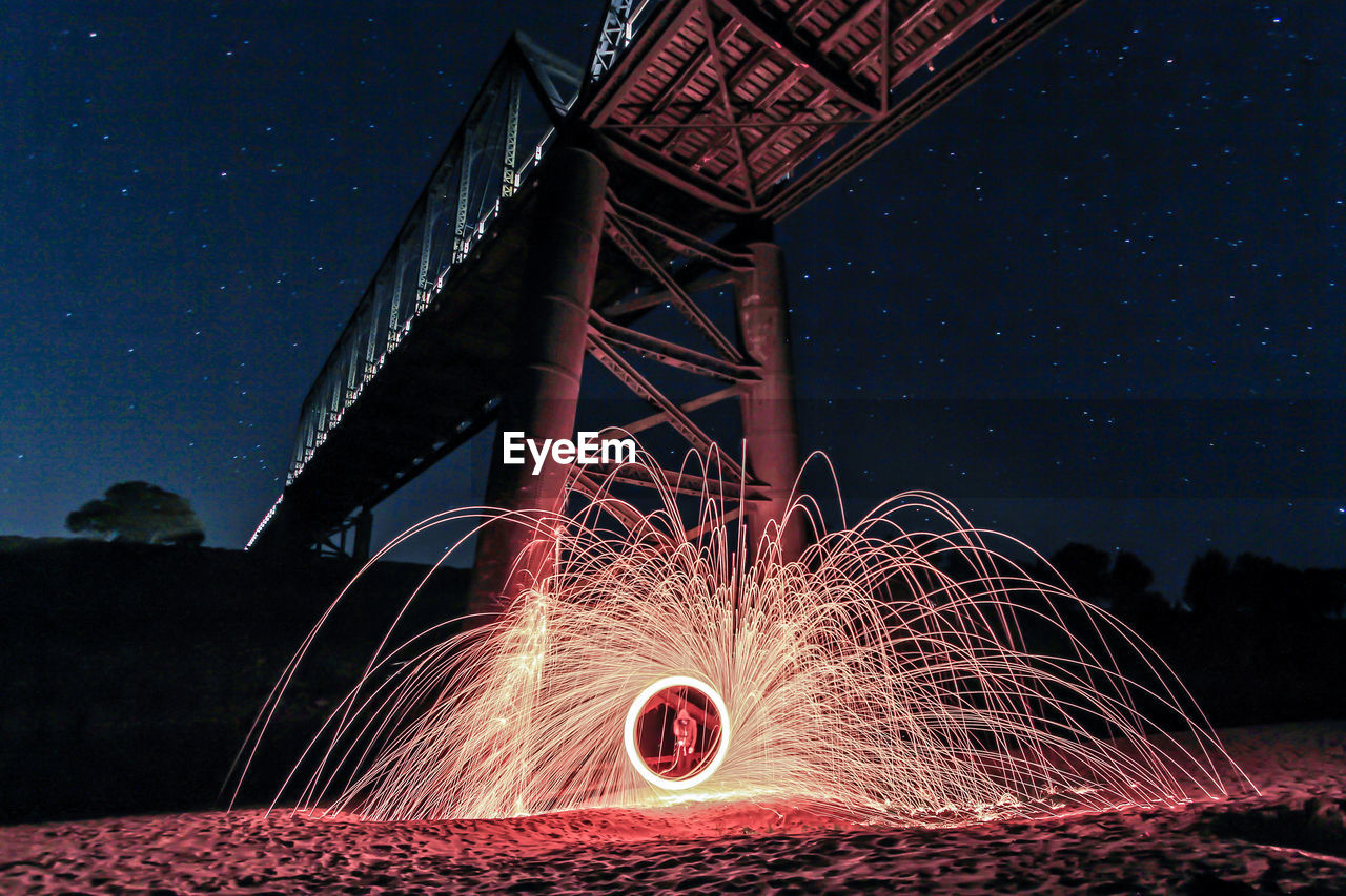 Person Light Painting Under Bridge At Night