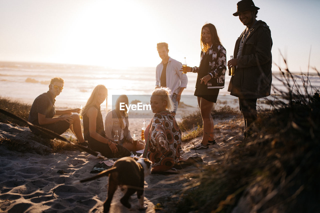 group of people, sky, land, beach, real people, sea, leisure activity, nature, water, togetherness, lifestyles, sunset, men, people, women, casual clothing, group, medium group of people, adult, outdoors