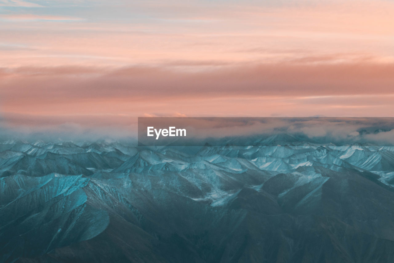 Aerial View Of Snowcapped Mountains Against Cloudy Sky At Dusk