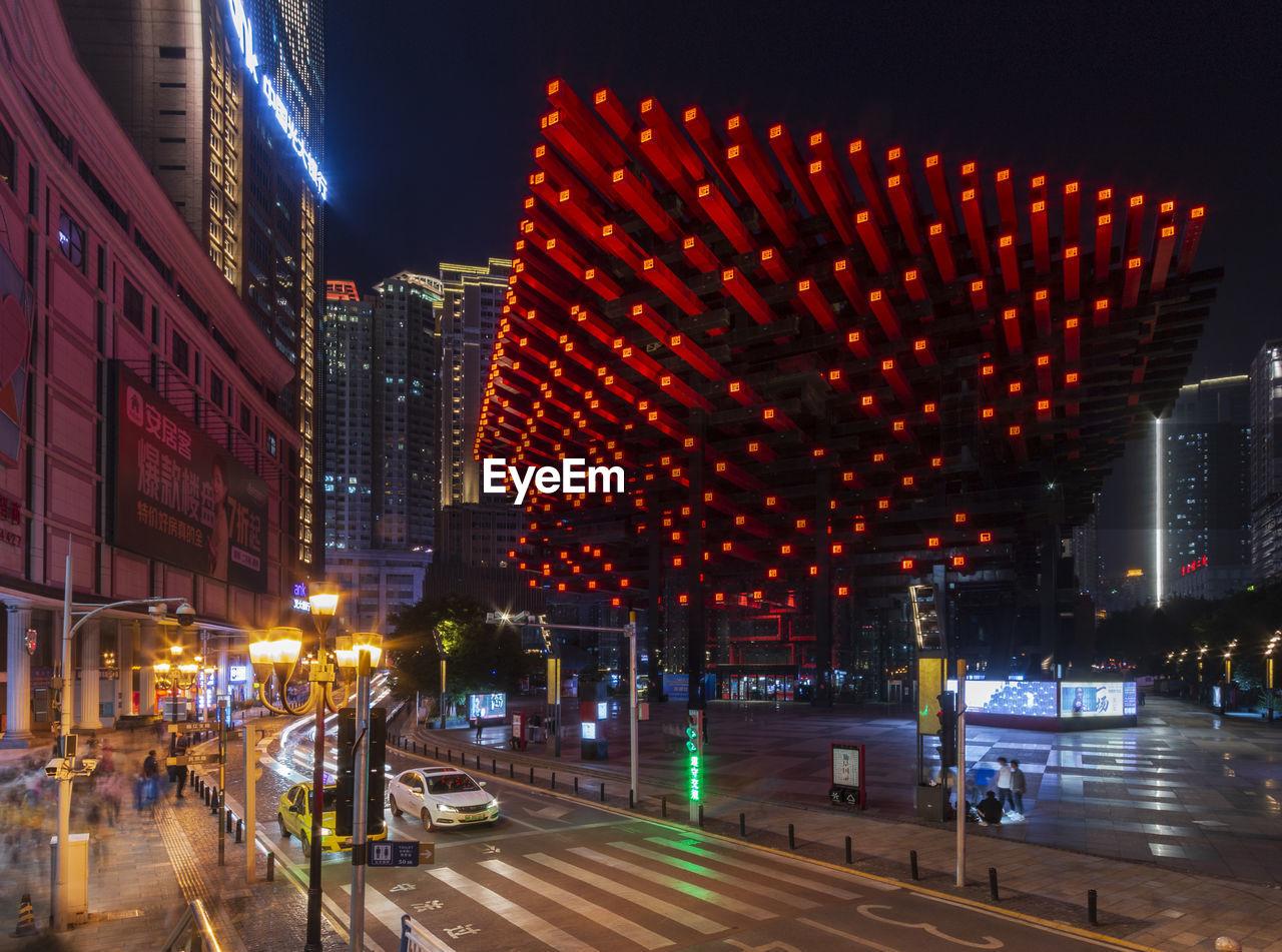 ILLUMINATED CITY STREET AMIDST BUILDINGS AT NIGHT