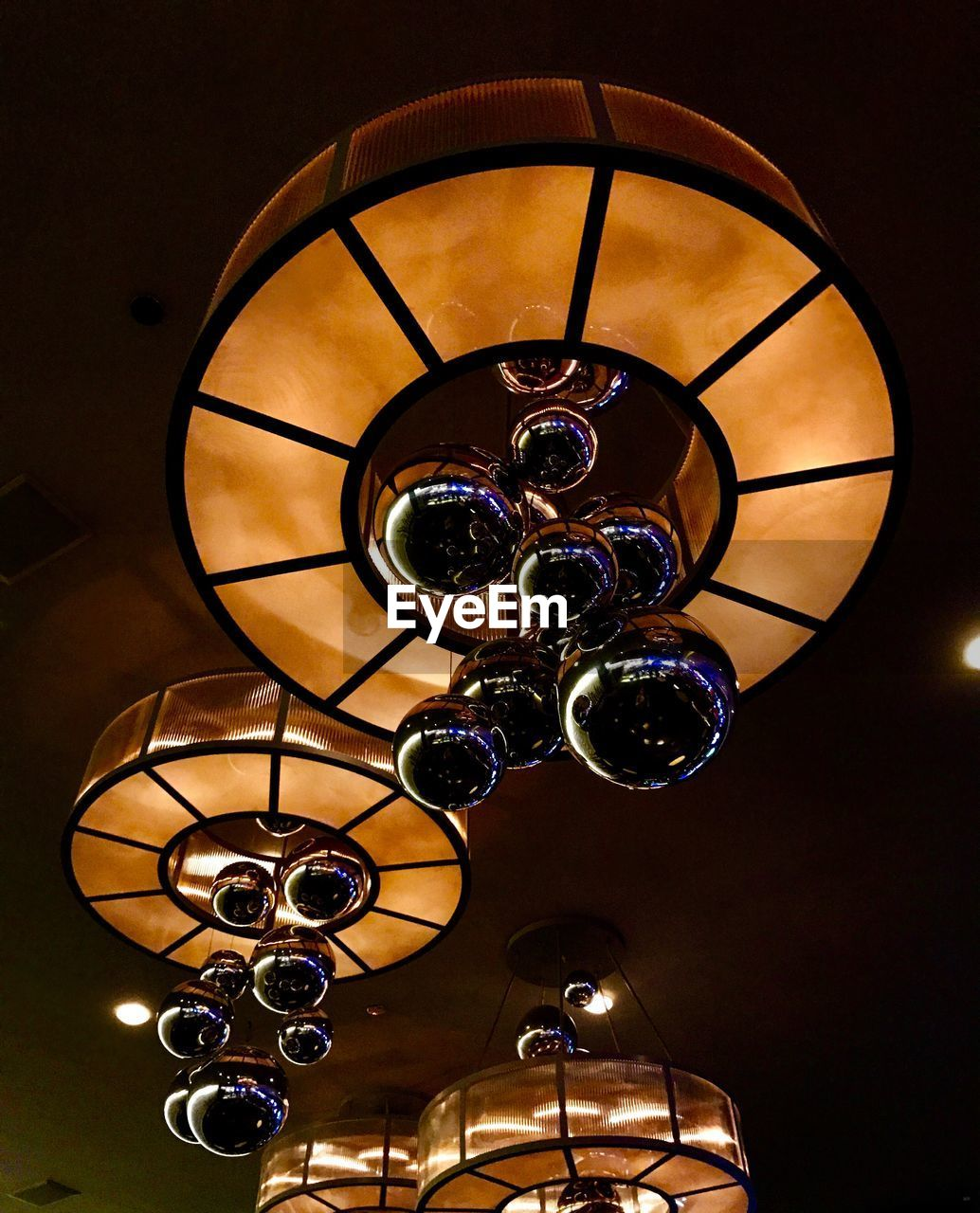 lighting equipment, indoors, ceiling, illuminated, low angle view, hanging, no people, pendant light, decoration, light, design, glowing, home interior, chandelier, electric lamp, wall - building feature, electricity, electric light, pattern, close-up, luxury, light fixture, ornate