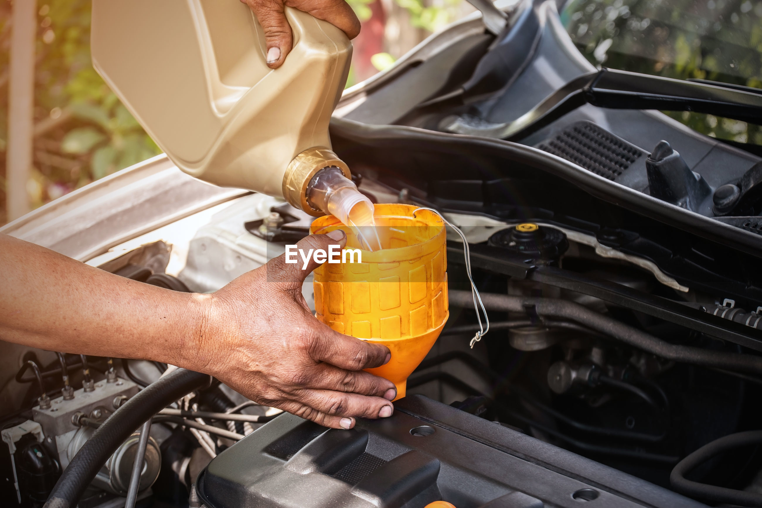 High angle view of hand pouring oil in car engine