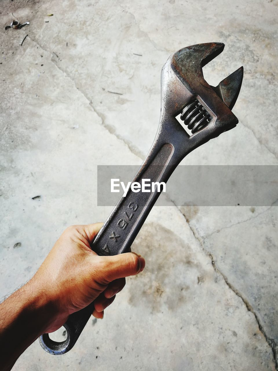 High angle view of person hand holding spanner