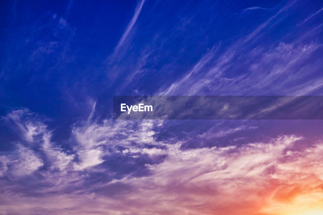 sky, cloud - sky, beauty in nature, blue, tranquility, low angle view, scenics - nature, backgrounds, nature, tranquil scene, no people, outdoors, idyllic, full frame, day, sunlight, sunset, environment, orange color, meteorology, wispy