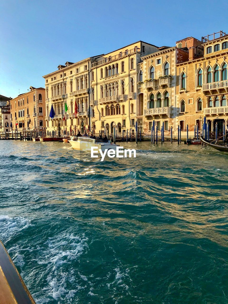 built structure, building exterior, architecture, water, sky, canal, city, waterfront, day, nature, building, residential district, motion, incidental people, travel destinations, clear sky, sunlight, sea, travel, outdoors, flowing water