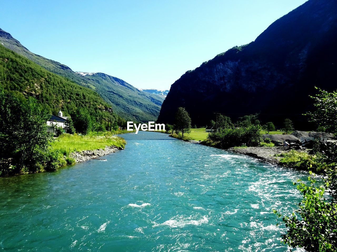River amidst rocky mountains against sky on sunny day