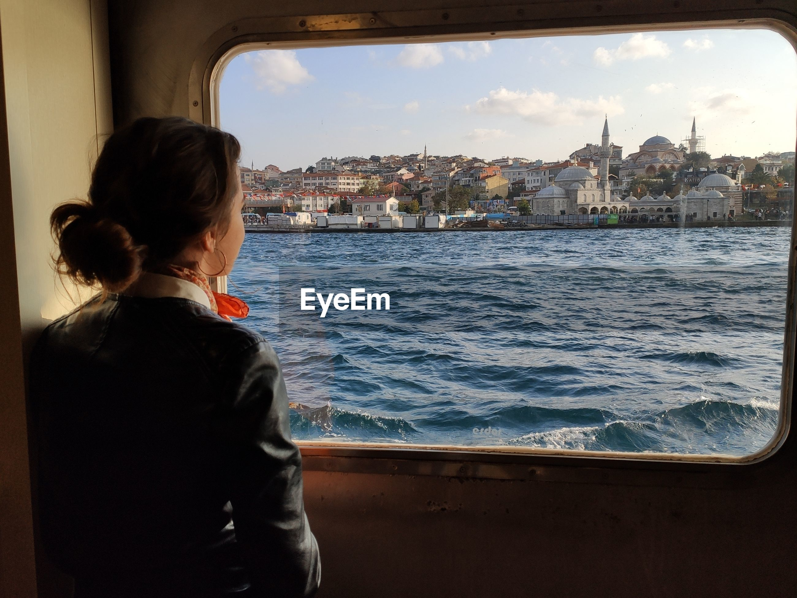 Rear view of woman standing by ferry window in city