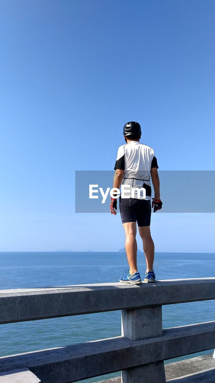 Rear View Full Length Of Man Standing By Sea On Railing