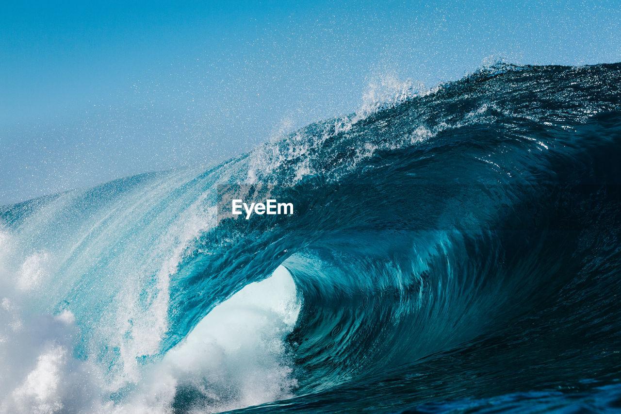 Waves splashing against blue sky