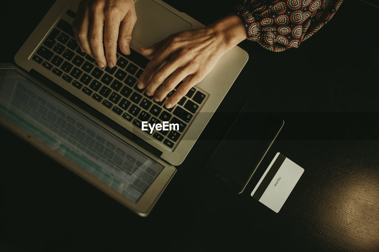 HIGH ANGLE VIEW OF HAND USING LAPTOP