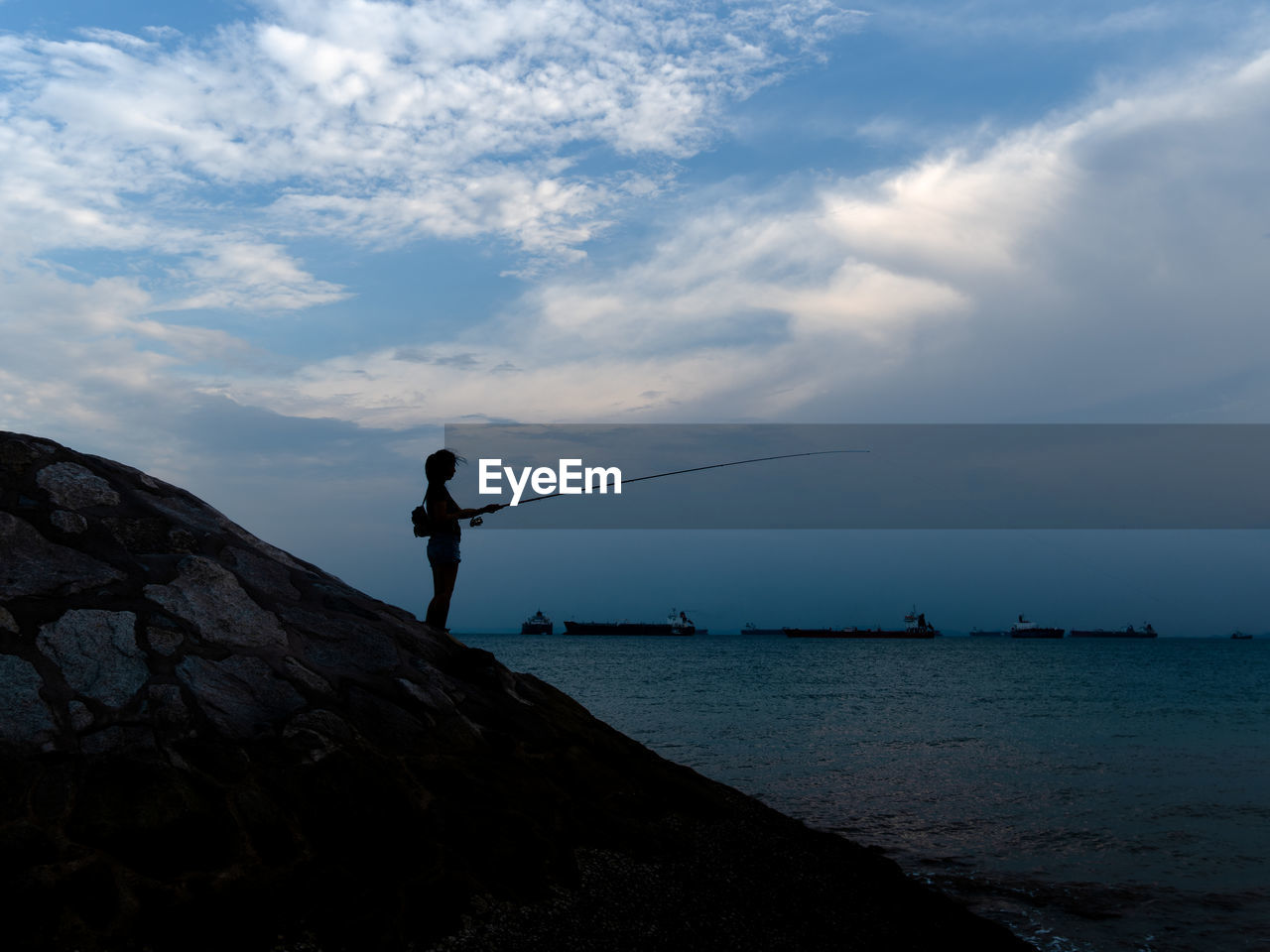 sky, cloud - sky, water, rock, sea, rock - object, real people, solid, leisure activity, beauty in nature, nature, scenics - nature, one person, standing, lifestyles, activity, fishing, outdoors