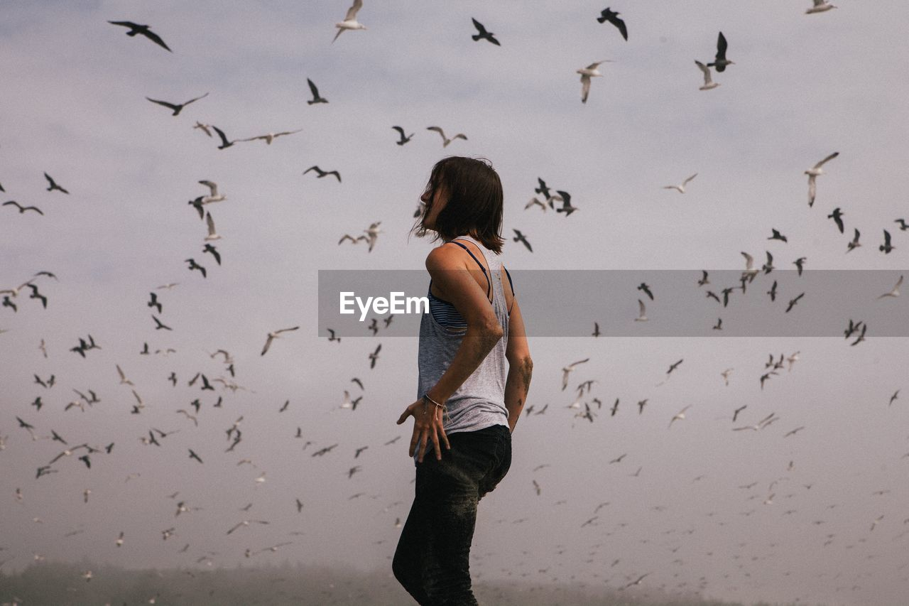 Side view of woman standing against birds