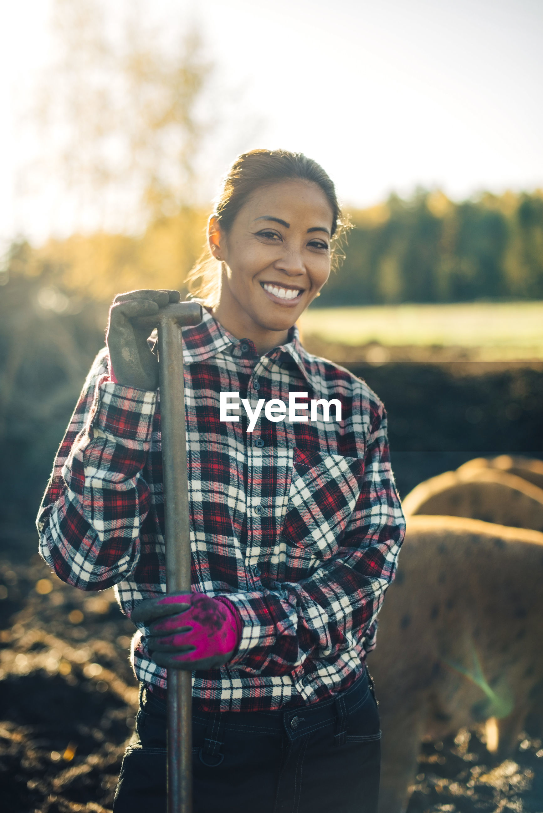 PORTRAIT OF SMILING YOUNG WOMAN STANDING ON LAND AGAINST THE BACKGROUND