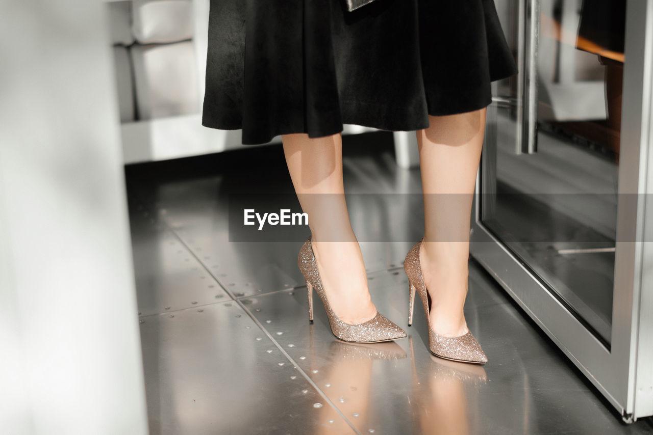 Low section of woman in standing on floor by door