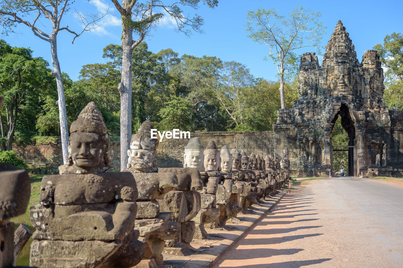 Statues by road against trees at angkor thom south gate