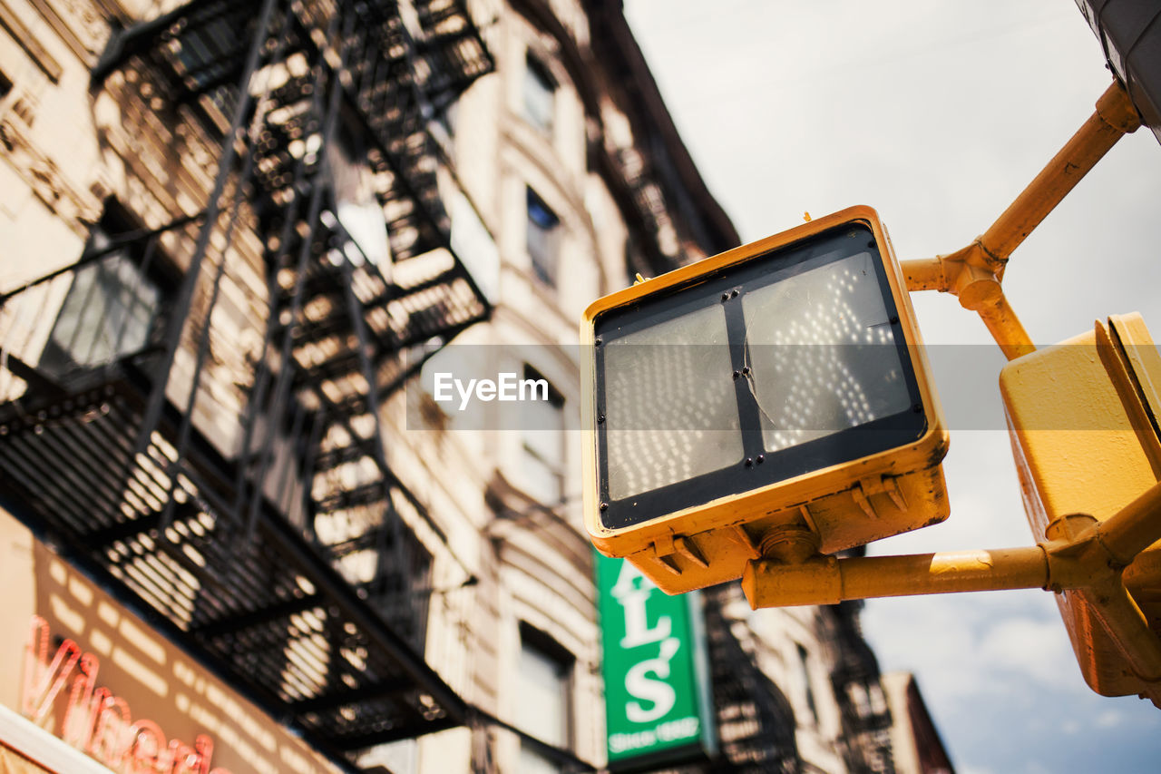 Low angle view of traffic signal against building and sky