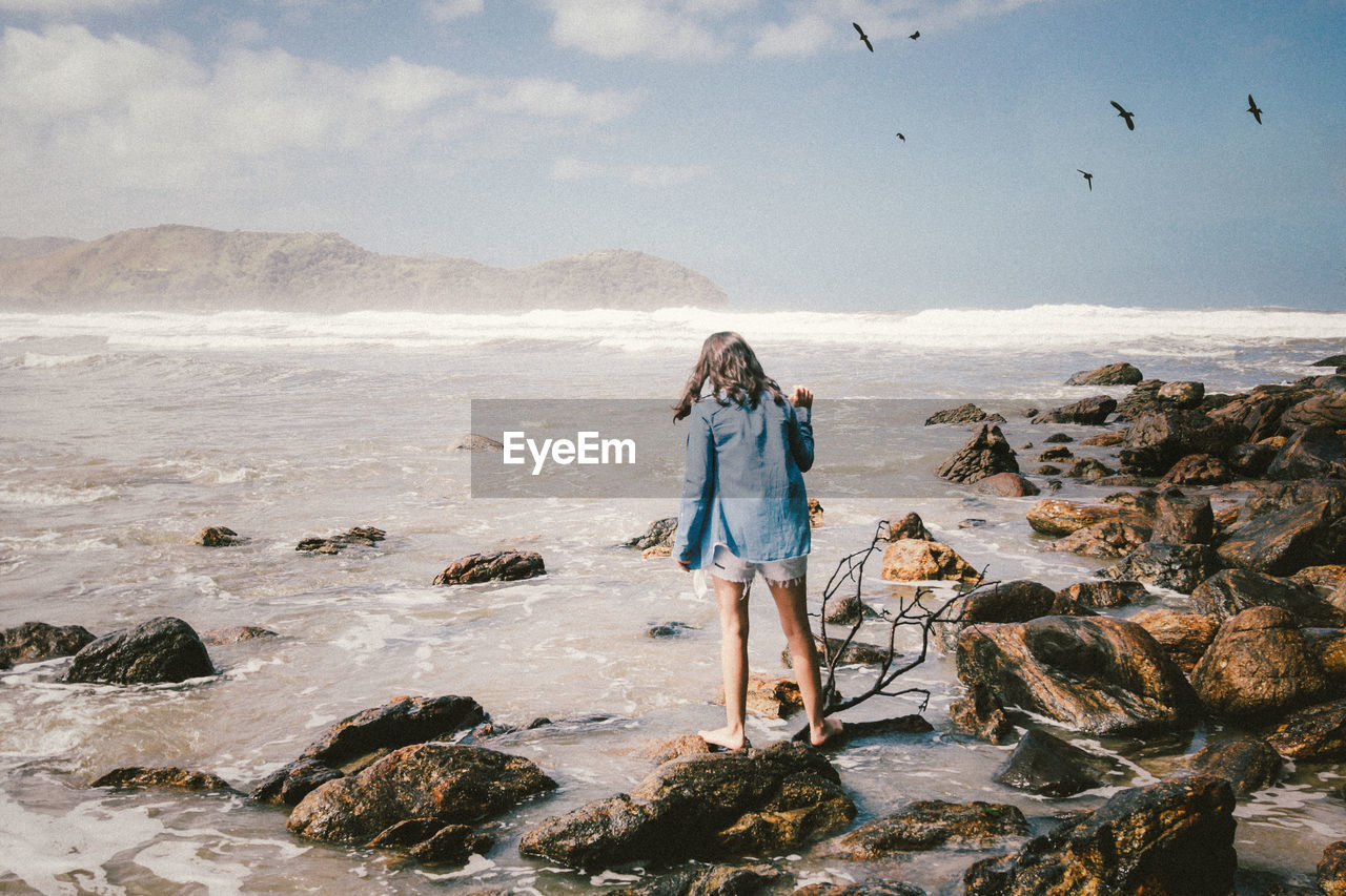 sea, rock - object, nature, standing, real people, rear view, sky, full length, beach, water, day, outdoors, one person, horizon over water, leisure activity, beauty in nature, scenics, sand, women, wave, bird, young women, young adult, people