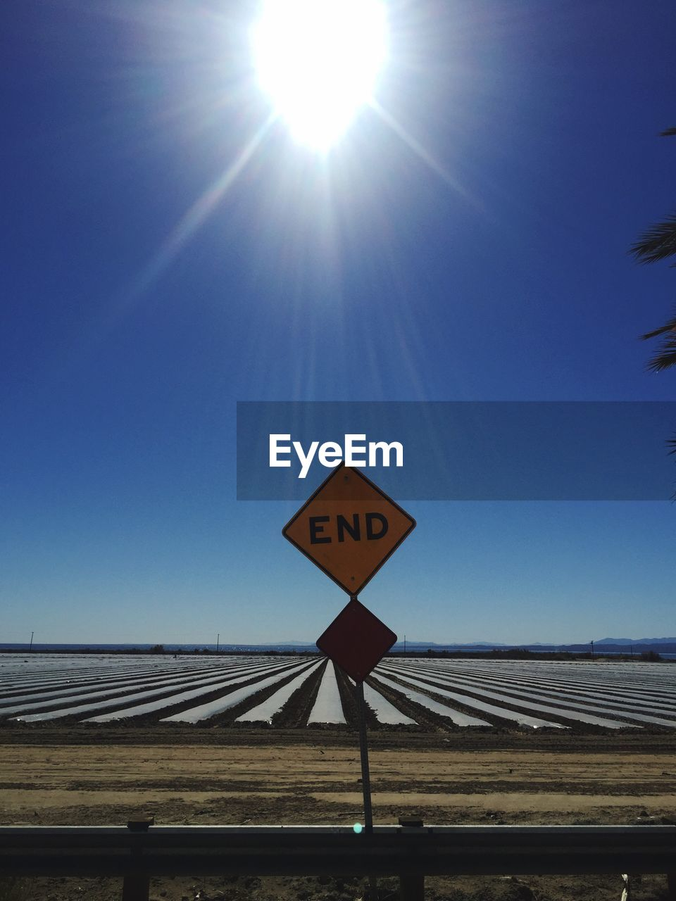 sunlight, communication, sun, lens flare, text, guidance, clear sky, road sign, day, blue, outdoors, sky, no people