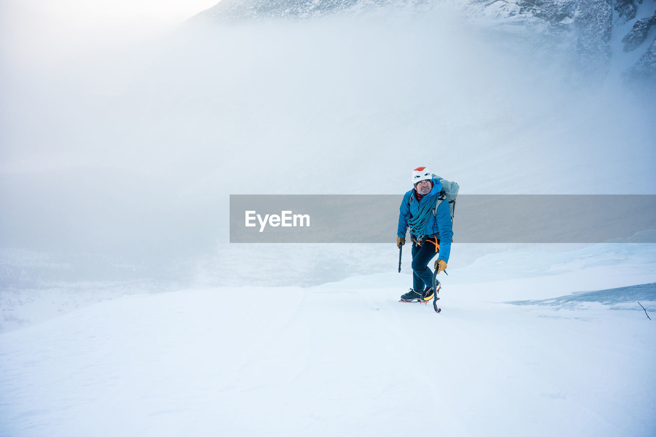 REAR VIEW OF PERSON ON SNOWCAPPED MOUNTAINS