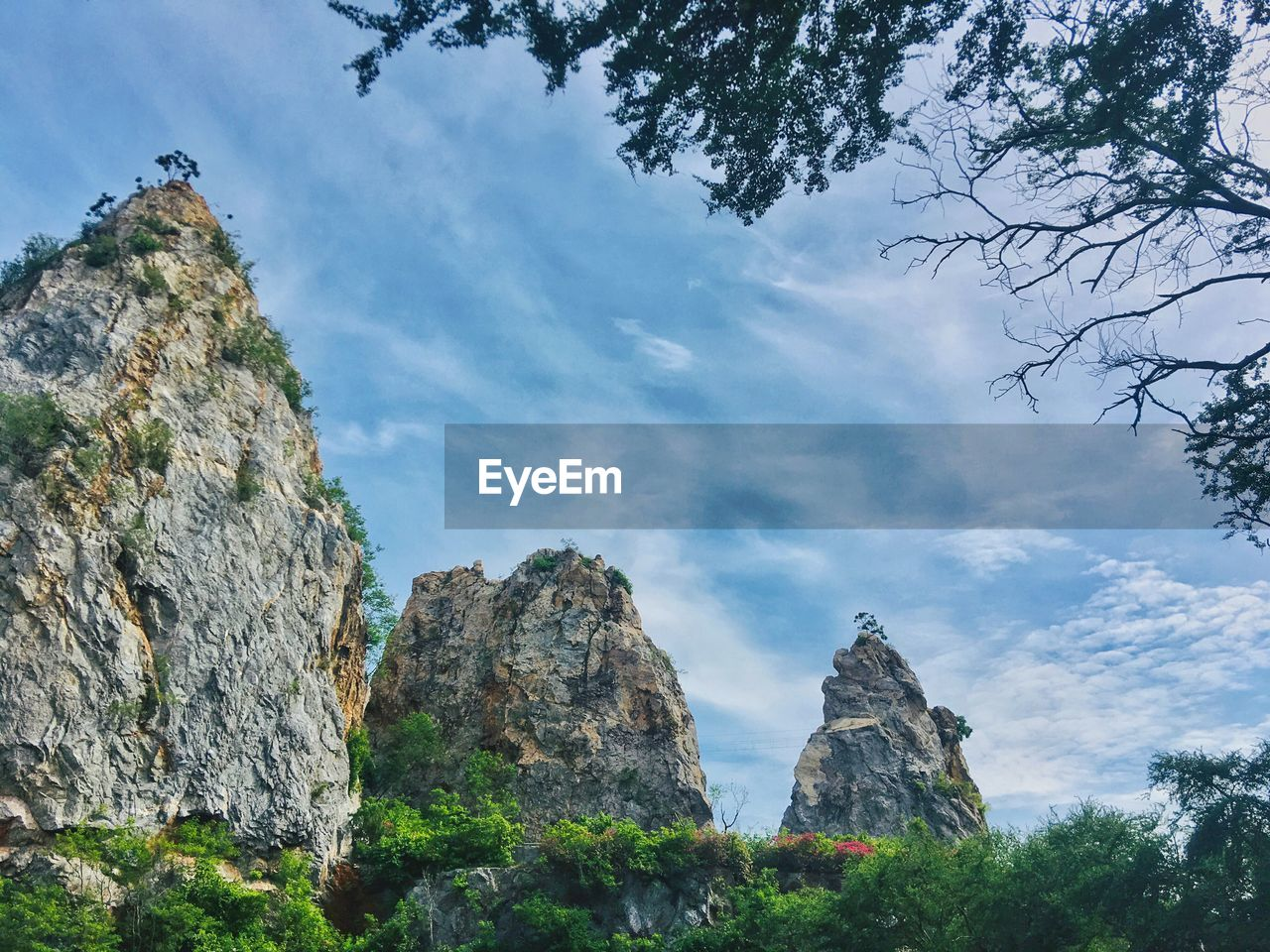 sky, rock, plant, cloud - sky, tree, low angle view, beauty in nature, rock - object, nature, rock formation, solid, mountain, tranquility, day, scenics - nature, tranquil scene, growth, no people, land, non-urban scene, outdoors, formation, mountain peak, eroded