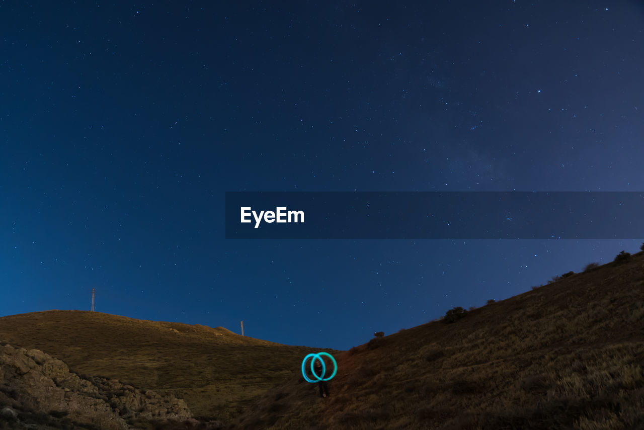 Low Angle View Of Person With Light Painting On Mountain At Night