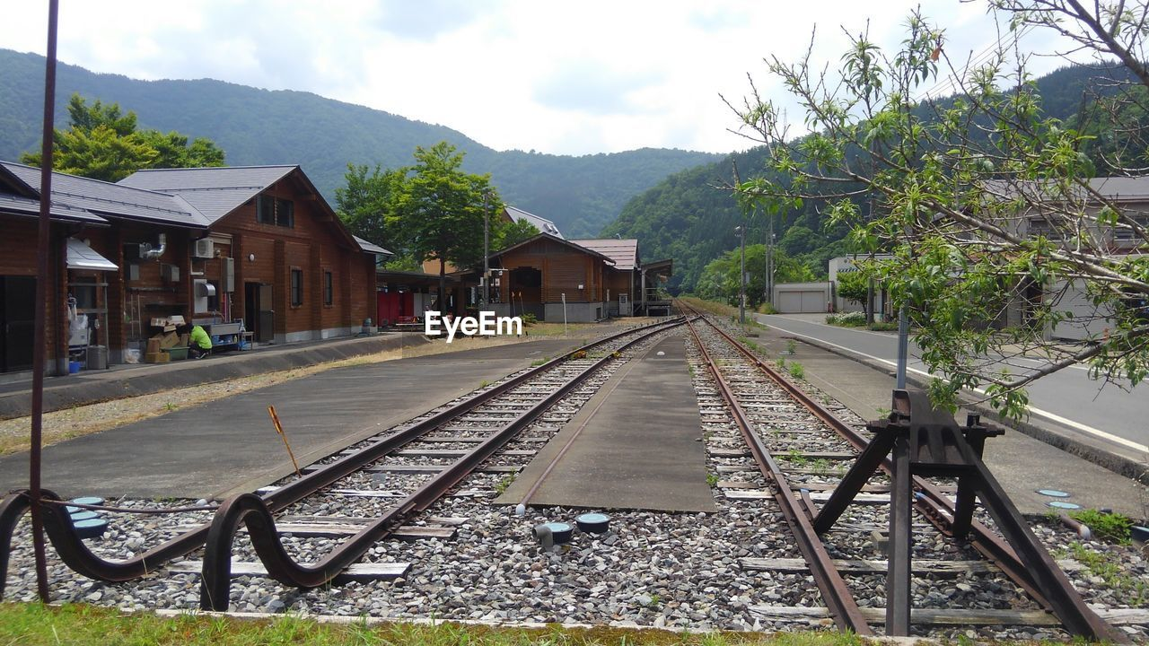 railroad track, transportation, rail transportation, built structure, mountain, architecture, sky, building exterior, day, outdoors, tree, no people, nature