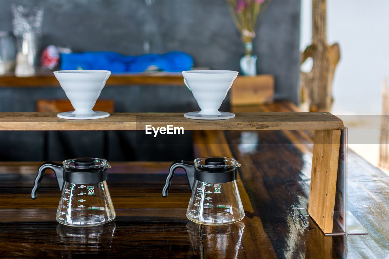 Jugs And Cups On Wooden Table At Cafe
