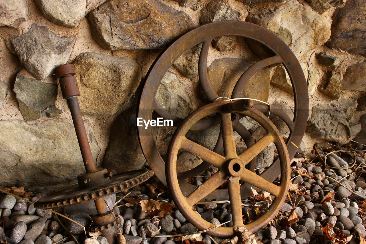 wheel, metal, no people, transportation, nature, old, solid, day, mode of transportation, obsolete, outdoors, abandoned, machinery, rusty, damaged, architecture, high angle view, stone wall, wood - material