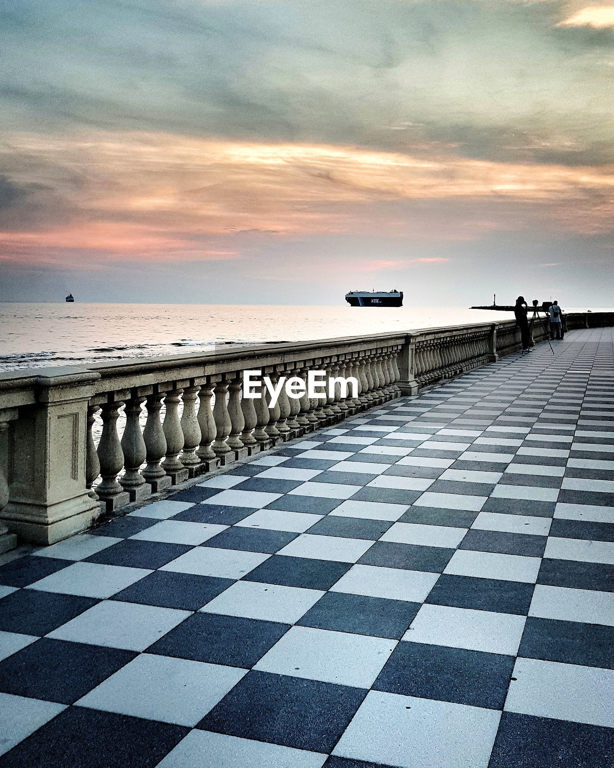 Sea seen from tiled floor against sky during sunset