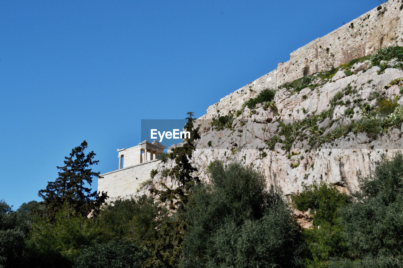 Low angle view of fort on mountain against clear blue sky