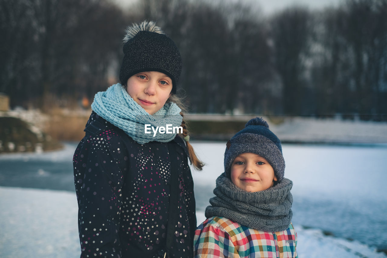 Portrait Of Cute Siblings Standing On Snow