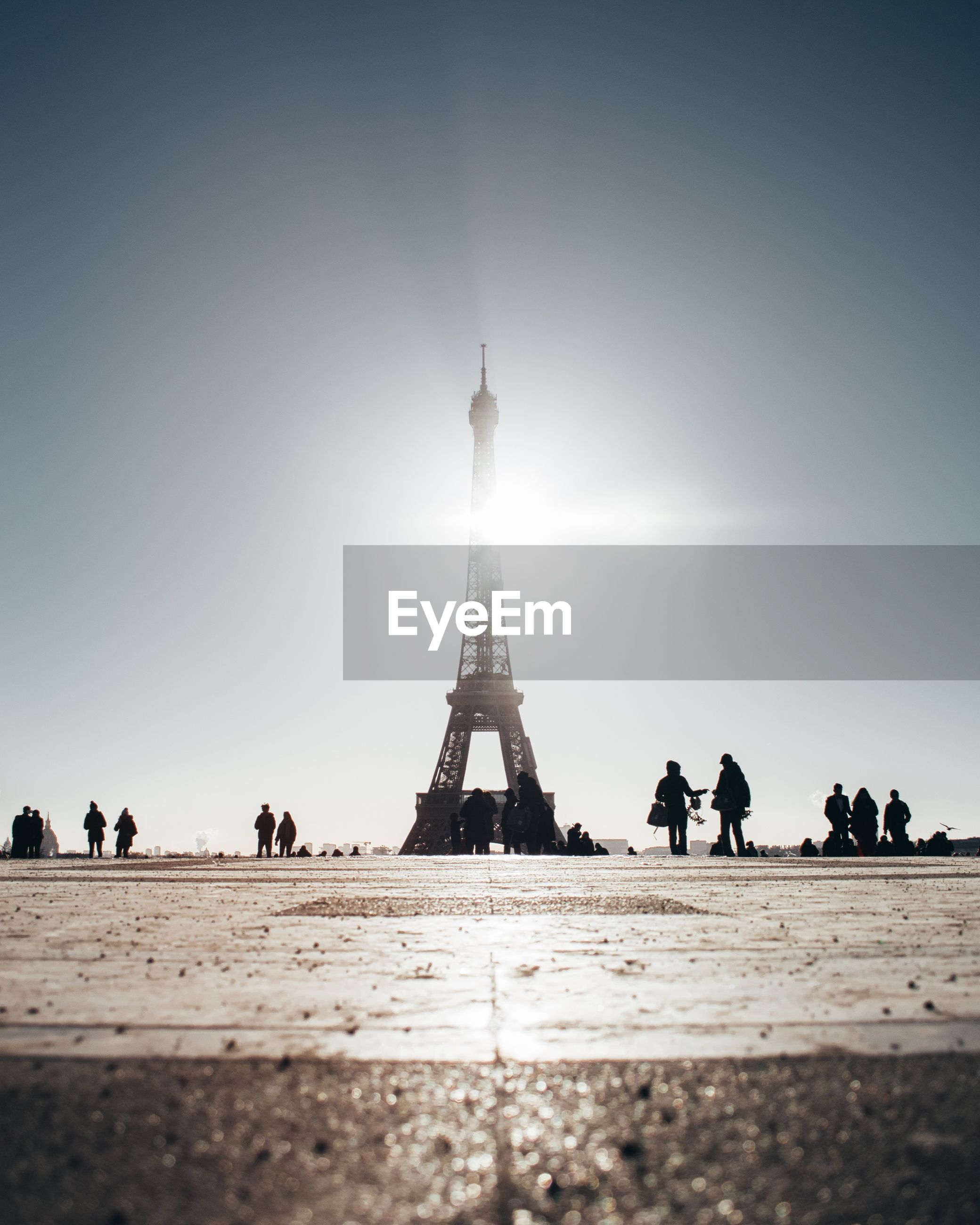 People in front of eiffel tower against clear sky